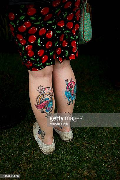 Detail of girl wearing cherry patterned dress showing tattoos on both calves at Goodwood on September 10 2016 in Chichester England