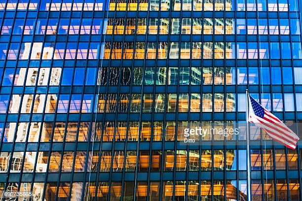 Detail of glass fronted skyscraper facade and American flag, New York, USA
