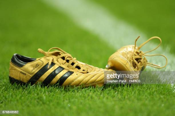 Detail of Golden Adidas football boots on the pitch