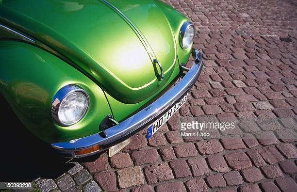 Detail of green Volkswagen parked on cobblestone street.