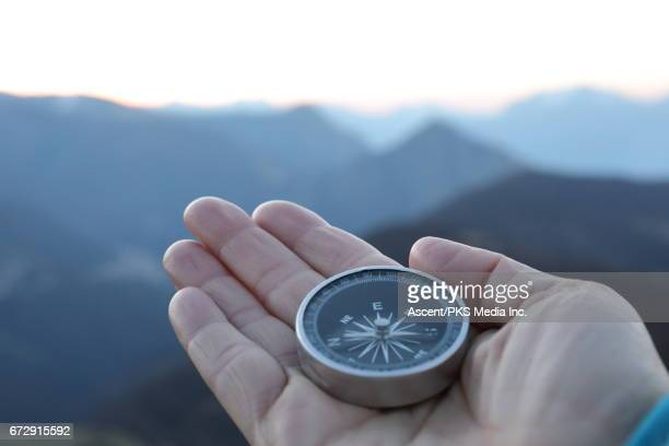 detail of hand holding compass on mountain summit - compass stock pictures, royalty-free photos & images