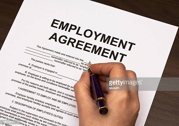 Detail of hand holding pen over employment agreement