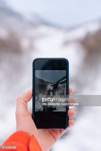 Detail of hand holding smart phone, taking picture