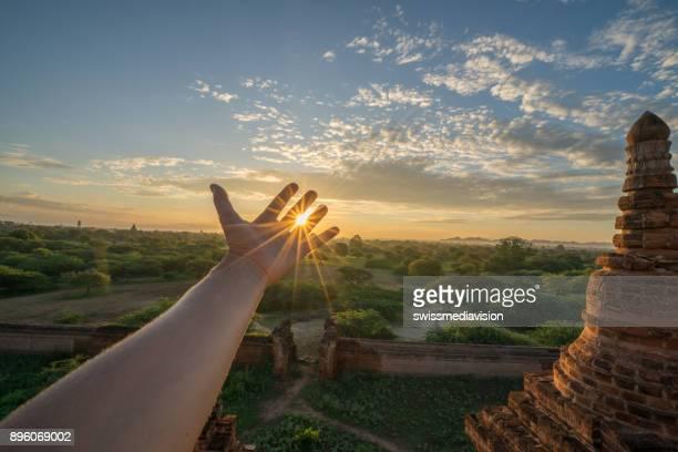 夕日、バガン、ミャンマーのカップの線を伸ばして手の詳細 - バガン ストックフォトと画像