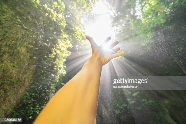 detail of hand stretched to cup rays of sunset - light at the end of the tunnel stock pictures, royalty-free photos & images