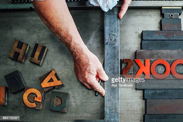 detail of hand using letterpress machine in book arts workshop, overhead view - typography stock photos and pictures