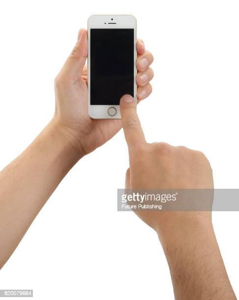 Detail of hands holding and pressing the touchscreen of an Apple iPhone SE smartphone taken on April 7 2016