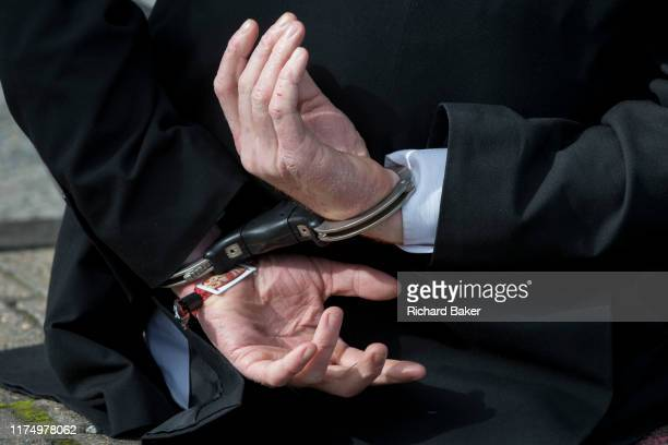 Detail of hands in handcuffs after an environmental activist has been arrested while protesting about Climate Change during the occupation of City...
