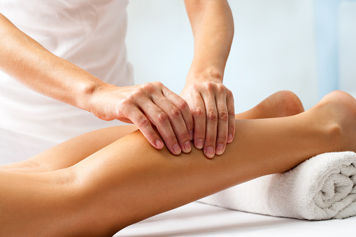 Detail of hands massaging human calf muscle. 487692350