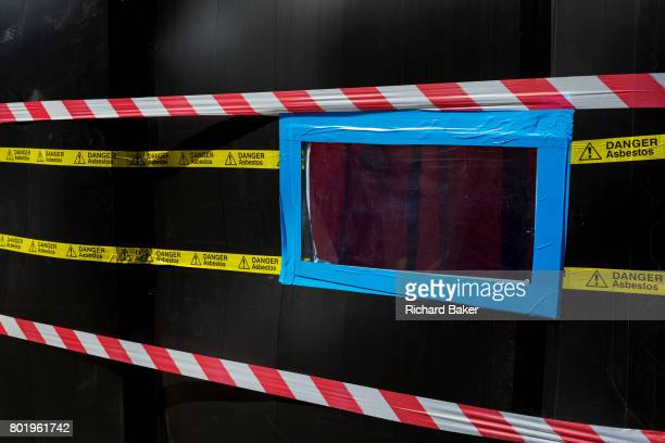 A detail of hazard tape marks the dangerous presence of Asbestos at a business at Spitalfields on 26th June in London England
