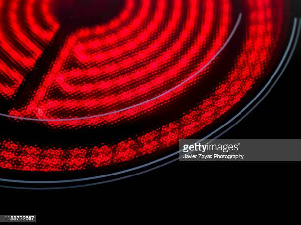 detail of heated ceramic stove top - electric stove burner stock pictures, royalty-free photos & images