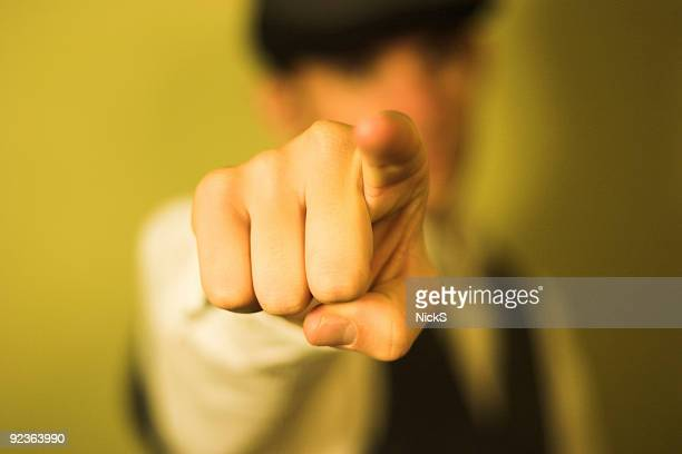 detail of man pointing index finger on yellow background  - blame stock pictures, royalty-free photos & images
