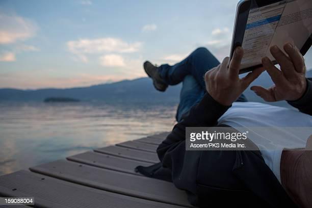 Detail of man using digital tablet on lake wharf