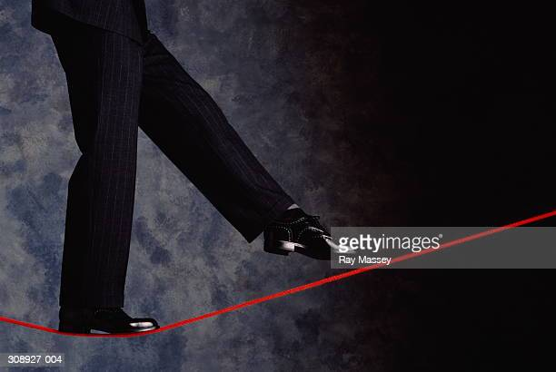 Detail of man's legs in business suit on tighrope,grey background