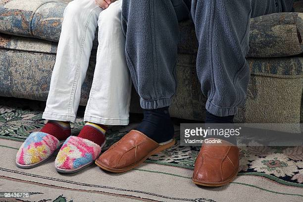 detail of mature couple sitting on sofa wearing slippers - old man feet stock pictures, royalty-free photos & images