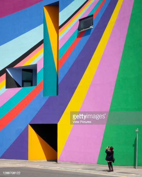 Detail of multi-coloured facade with figure taking picture. The Towner Gallery, Eastbourne, United Kingdom. Architect: Rick Mather Architects, 2009.