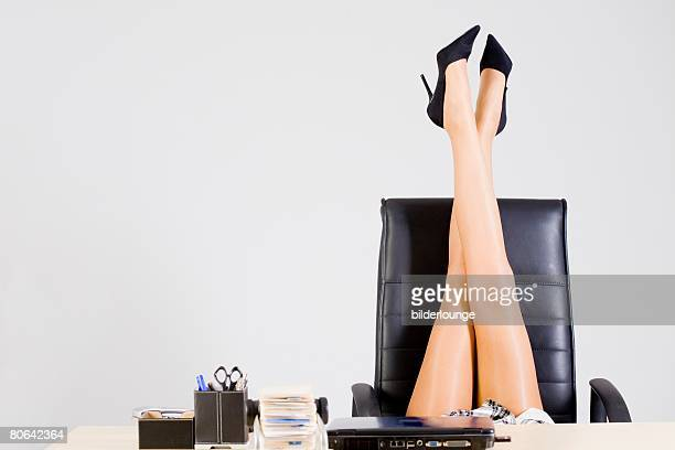 detail of office worker at desk putting her legs in the air