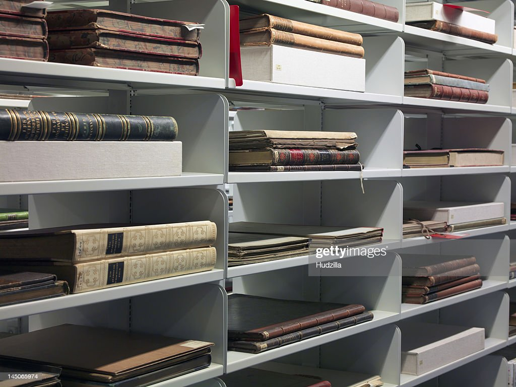 Detail of old books on shelves in a library : Stock Photo