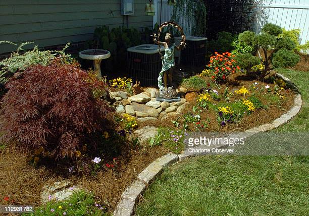 Detail of one corner with statue and stone border in Matthew and Grace Savage's beautifullylandscaped tenthofanacre yard which is perfect proof that...