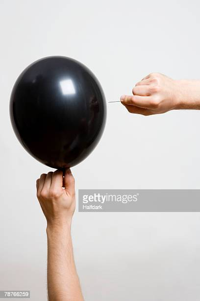 Detail of one person holding a balloon and another person holding a pin