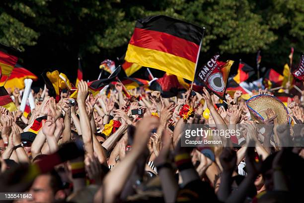 Detail of people in a crowd waving German flags