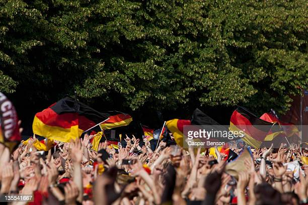 detail of people in a crowd waving german flags - german flag stock pictures, royalty-free photos & images