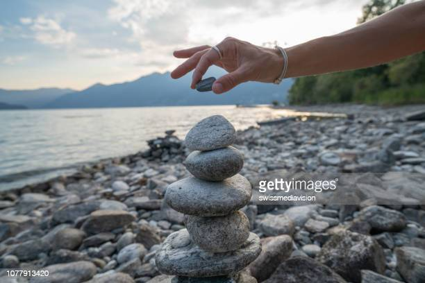 detail of person stacking rocks by the lake - alternative medicine stock pictures, royalty-free photos & images