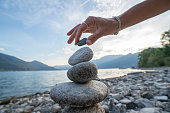 detail person stacking rocks lake shot