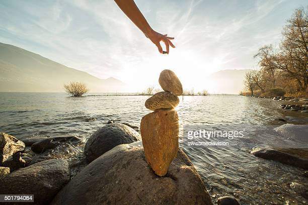 detail of person stacking rocks by the lake - alternatieve geneeswijzen stockfoto's en -beelden