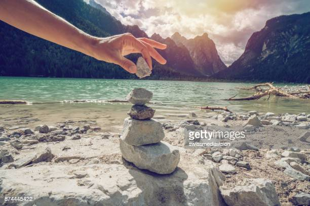 detail of person stacking rocks by the lake - pietra roccia foto e immagini stock