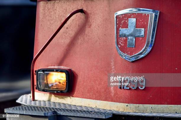 Detail of Red Swiss commuter train on platform at Zurich Central Station, with coat of arms of Switzerland on front of train