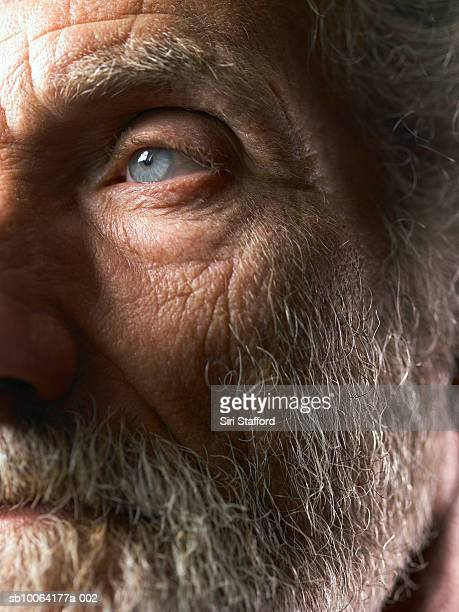 Detail of senior man's face with grey beard and blue eyes