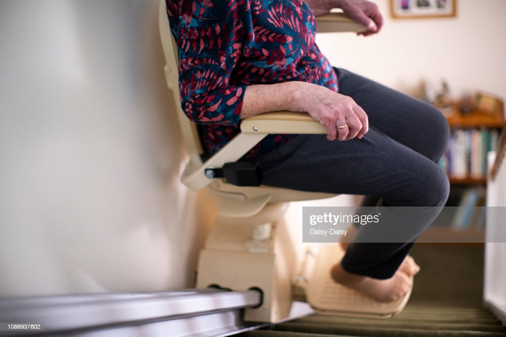 Detail Of Senior Woman Sitting On Stair Lift At Home To Help Mobility : Foto de stock
