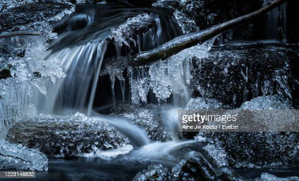 detail of smell waterfall in a forest creek with frozen rocks and icicles. - arne jw kolstø stock pictures, royalty-free photos & images