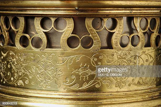 Detail of the decoration on a crucifixshaped gilt brass clock with cast moulded figures rocker arm mechanism on which is mounted a springloaded cam...