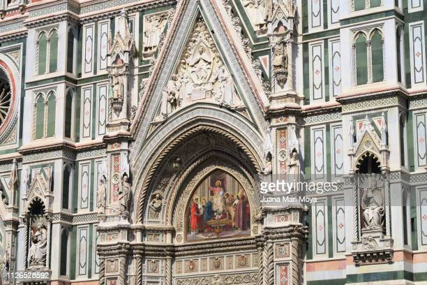 Detail of the enormous facade of Santa Maria del Fiore cathedral.  In the Piazza del Duomo in Florence, Italy