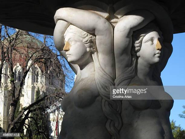Detail of the fountain popularly called the Three Graces at the door of Hernani in Retiro Park in Madrid and the background neoByzantine style Church...
