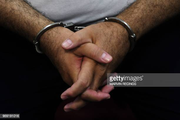 Detail of the hands of former Salvadoran President Elias Antonio Saca with handcuffs taken as he waits along with six of his collaborators for the...