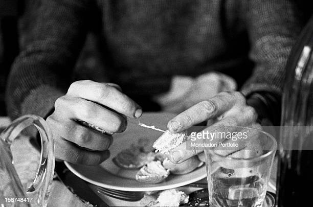Detail of the hands of Italian violinist Uto Ughi peeling a mandarine orange Val Badia January 1970
