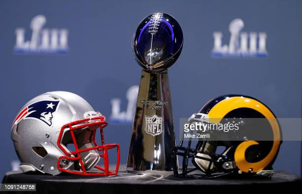 Detail of the Lombardi Trophy and the helmets of the New England Patriots and the Los Angeles Rams prior to NFL Commissioner Roger Goodell speaking...