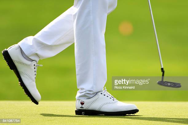 A detail of the shoes of Gregory Bourdy of France showing a glass of red wine during the third round of the US Open at Oakmont Country Club on June...