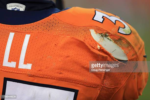 A detail of the shoulder pad and torn jersey of running back Lance Ball of the Denver Broncos as he faces the Arizona Cardinals during preseason...