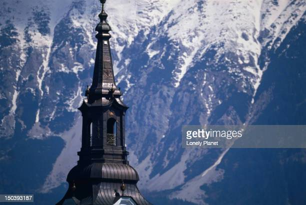 Detail of the spire atop the belfry of the baroque Church of the Assumption on Bled Island, behind which are the majestic snow-capped Julian Alps.