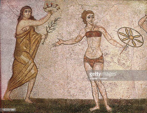Detail of the Ten Girls Mosaic depicting women athletes A girl clad in a golden mantle carries a palm leaf and a rose crown for the winner From the...