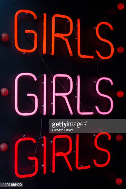 A detail of three Girls words repeated in neon in the doorway of an adult shop in Soho on 5th March 2019 in London England