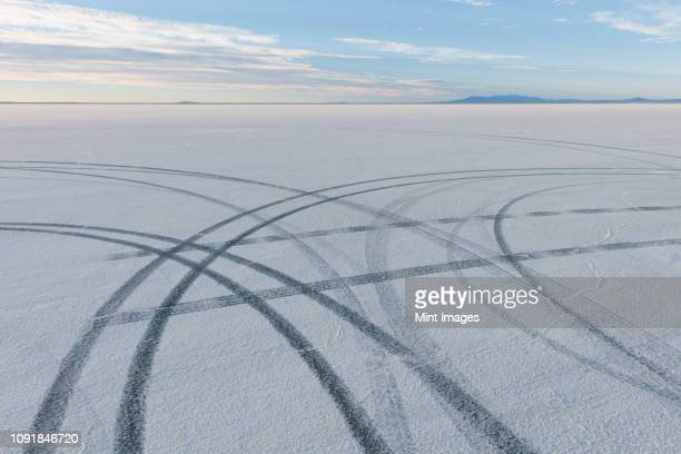 detail of tire tracks on salt flats at dawn - track imprint stock photos and pictures