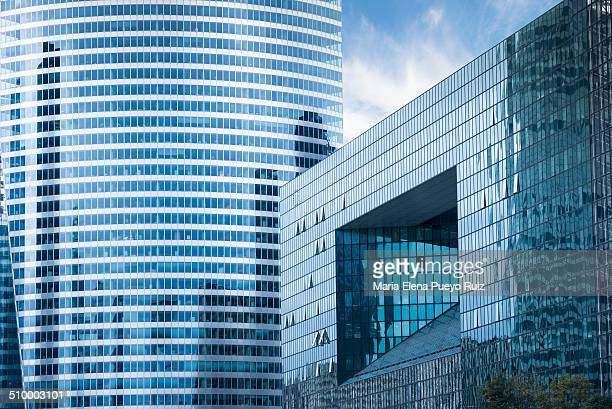 Detail of two blue and glass skyscrapers in La Defense, Paris.