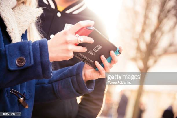 Detail of two people playing video games on a Nintendo Switch home console outdoors, taken on March 2, 2017.