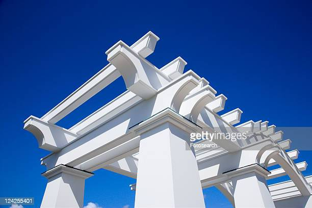 Detail of white arbor against blue sky.