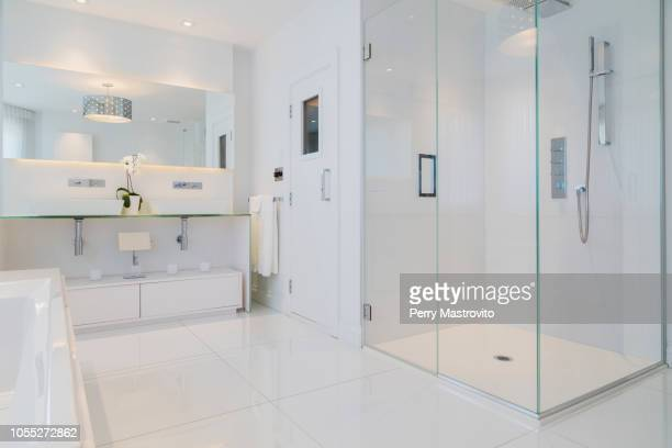 detail of white rectangular bathtub, wall mirror, glass shower stall and sauna room door in en suite with ceramic tile flooring, upstairs inside luxury residential home - domestic bathroom stock photos and pictures